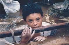 Omaira Sanchez (12) is trapped in the debris caused by the eruption of Nevado del Ruíz volcano. After sixty hours she eventually lost consciousness and died of a heart attack. (Frank Fournier)