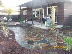 This dry-laid flagstone patio was blended to a lawn with a lava rock bed.
