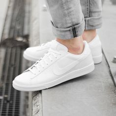 plain white nike lace up sneakers, worn by a person, dressed in pale grey jeans, what is a capsule wardrobe, basic everyday clothes and shoes