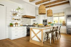 The classic white kitchen gets a fresh update from floor-to-ceiling wood embellishments, including a band of reclaimed boards around the sleek range hood.