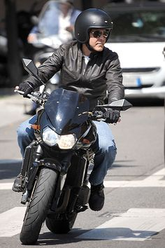 George Clooney rides a motorcycle in Milan, Italy.