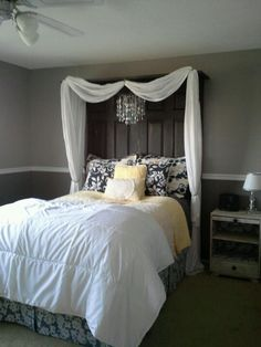 Bed with lace on top and headboard made from old doors. Shelf on top and curtains hanging from each side using small hooks. Electric chandelier hanging from center