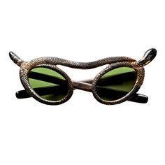 A rare and fabulous French pair of snake sunglasses by Paulette Guinet circa early 1950's. Hand Carved with a great scaly texture with parcel gilt as the head and tail create the cat eye points of the glasses. Oh so French!
