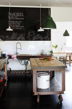 Industrial metal and wooden topped kitchen island on oversized castors. Industrial style free standing kitchen units.White gloss tiles add a clean look to the rustic/industrial furniture. A feature blackboard on the wall adds an individual touch with hanging pendant task lighting. A painted black wooden floor finishes the look.