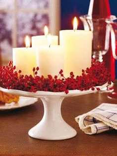 Use a cake stand to create a festive centerpiece. Here unscented candles surround red berries.