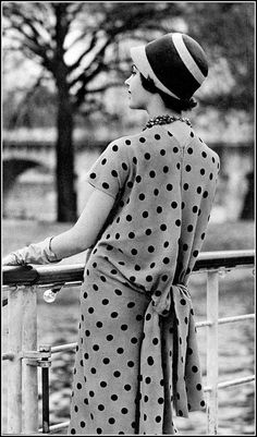 Model in charming dress of beige crêpe with black polka-dots, gathered in blouson and tied in back, by Jacques Griffe | Photo Georges Saad, 1958