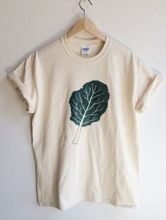 Hand Printed and Hand Drawn! Show your love of greens with this 100% cotton screen printed t shirt. It features a large hand drawn kale leaf. It is