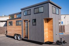 A contemporary tiny home on wheels from California Tiny House. The 24' home has a ground floor bedroom, two lofts, a living and dining room, full kitchen, and a bathroom.