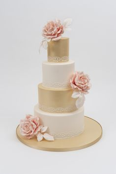 Gold and ivory 4 tier wedding cake with hand-piped lace and peach roses.