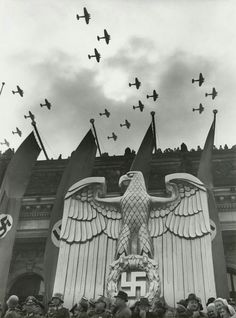 A very seldomly viewed yet brilliantly shot photograph of a great, metal imperial eagle under large, blood red swastika banners as the Luftwaffe fly in formation overhead.