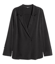 Black. Straight-cut blouse in crêped woven fabric with lapels, covered button at front, and a rounded hem. Long sleeves with wide cuffs with a slit and