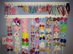 Nala's new bow holders.  Made only from a piece of molding & hooks!  PERFECT to hold her headbands & Pony-O's.. plus I got tired of having tons of different hair bow holders hanging everywhere.  :)  Oh, and I made nearly all the bows hanging - go me!