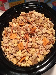 Start by mixing all the cereal, pretzels, Cheez-Its, and nuts in a large crockpot.