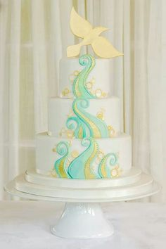 White cake with mint green & yellow designs & dove topper