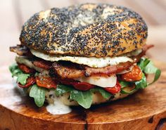 This meal of a sandwich brings crisp greens, oven-dried tomatoes, roasted chicken, peppery bacon, and a fried egg all together on a poppy seed bagel.