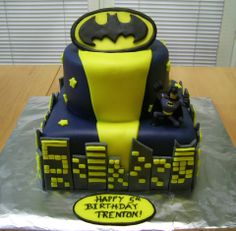 Batman Birthday Cake - Two-tier cake covered in dark blue fondant.  Fondant buildings, stars and Batman symbol.  The Batman figure is a toy figurine.