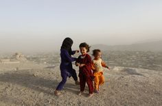 An Afghan child covers herself as others close their eyes during a dust storm at a hilltop in Kabul