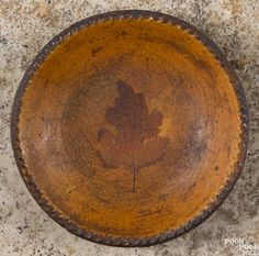 Pennsylvania redware pie plate, early 19th c., with central dark orange glaze of a leaf - Price Estimate: $200 - $400