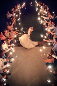pareja de novios besandose y alrededor sus invitados con luces de bengala