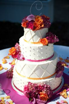 Orange and purple wedding  cake.   #2--Maybe this would be the way to go since the cake will be on  a black damask tablecloth Use black lines and colored ribbons--multi like on the cake?