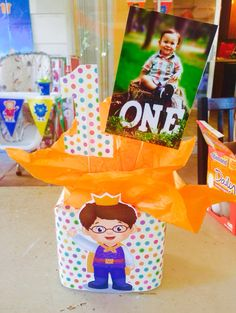 Daniel tiger centerpiece. Used empty similac container, wrapped with decorative paper and drilled holes on top for tissue paper, photo and #1 sign.