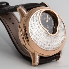The Logical One Secret features the quadruple-patent-pending Romain Gauthier flat chain-and-fusee style constant force system with ruby chain links, ergonomic push button winding system, dial-side visible balance, mainspring barrel with sapphire inserts, plus a 60-hour power reserve indicator.  The cover and lugs are adorned with 181 invisibly set baguette diamonds, totally nearly 7 carats.  For more information on the collection, please visit: http://www.romaingauthier.com/collections/