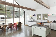 Floating farmhouse kitchen dining area: The table is situated in front of the house's rear wall of skyscraper glass. Laminate kitchen cabinets by Ikea are framed in wraparound bluestone; the 48-inch commercial range is by FiveStar.  Photo by: Mark Mahaney      Read more: http://www.dwell.com/slideshows/hope-floats.html?slide=4=y=true##ixzz2677FbxWF