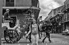 """Local kids on their way home from school"" photo #2. 5.3.2016 New Orleans Louisiana. On the corner of Royal & St. Peter there was a bubble machine set up outside a market. I watched adult after adult walk hurriedly through the bubbles many of them swatting at them as if they were mosquitos or something that might seriously mess up their hair or clothes. Then along came this little girl- she stopped & just started freaking out at the awesomeness of all the bubbles in the air even trying to…"