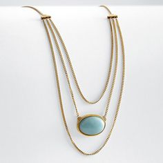 Late-19th-century overtones combine with modern simplicity of design in this dramatic piece. Swags of antiqued gold-plated chain have an elegant drape and movement, framing the large-scale bezel-set amazonite centerpiece. Ancient token of integrity and sincerity, the stone is as meaningful as it is striking in its robin's-egg-blue hue.