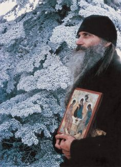 Father Seraphim Rose holding an icon of the Holy Trinity