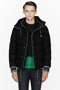 MONCLER //  Black quilted wool Bresle jacket  32111M030011  Long sleeve quilted wool jacket in black. Grey knit trim throughout. Removable hood with tonal drawstring. Two-way zip closure at front concealed by press-stud placket. Flap pocket and welt pockets at front. Welt pocket at interior. Fully lined. Tonal stitching. Ribbed knit sleeve cuffs. Shell: 100% wool. Lining: 100% polyamide. Filling: 90% down, 10% feather. Dry clean. Imported.  $1495 CAD