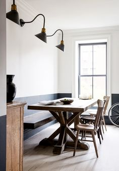 Black and white dining space with industrial wall sconces