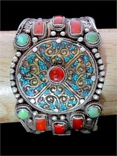 An Old Tibetan Tribal Cuff Bracelet...handcrafted early to mid 1900's. This unusual museum quality piece was ornately made of quality Silver with Turquoise and Red Coral beads set in raised silver bezels. More inlaid Turquoise adorns front section, setbetween intricate scrolls of brass. Stunning craftsmanship along the entireband