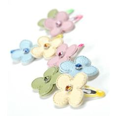 Doll up your darling dogs' hair with a Floral Diamond Dog Clip.        Leather flower with faux diamond in center.      Snap barrette style clip.       Why We Love It:    Dress up your gorgeous girl with these Floral Diamond Dog Clips from Gooby! These flower-shaped clips have a matching faux diamond jewel in their center. Clips come in a set of eight. In each pack, there are two blue, two lime, two yellow, and two pink snap barrette style clips for dogs.