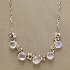 "Raindrops of moonstone and paillettes of hammered sterling glisten on a light sterling chain. 16""L."