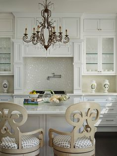 An iron chandelier illuminates a square kitchen island topped with white marble lined with a pair of cream wood scroll counter stools adorned with gray dot seat cushions. Kitchen Nook, Kitchen Decor, Kitchen Ideas, Pantry Ideas, Elegant Kitchens, Beautiful Kitchens, Square Kitchen, Kitchen Chandelier, Interior Decorating
