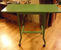 Vintage Green Typewriter Table - This is a vintage typewriter table in great condition. It is made of solid steel, has been painted a cheerful green, and its wheels turn easily. Great as a side end table, kitchen stand, desk extension, or to display your antique typewriter!  Dimensions: 18″W (w/o leaf) x 14″D x 27″H. Each extension side adds 8 inches to the width. *SOLD*