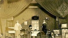 Geschiedenis van Vlaardingen - Gedempte Biersloot, tentoonstelling in gebouw van 'Liefde en Vrede'. Op het toneel van de tentoonstellingsruimte werd een oud-Vlaardingse kamer ingericht met twee poppen in Vlaardingse klederdracht. Foto Borg, 1933 #ZuidHolland #Vlaardingen
