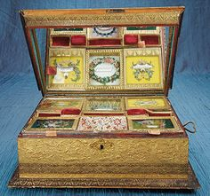 This musical sewing box is decked out in embossed gilt papers, sports a mirror and removable trays, and contains many little treasures, including a little embroidered friendship card.