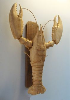 """We simply love this exceptional carved lobster and what a great looking wall hanging. I think this lobster could be equally as interesting as a table centerpiece! Shown wall mounted with an adjustable metal bracket and attached to a piece of old weathered dog-eared board from a beach fence (optional). A wonderful folk art carving by Jac & Patricia Johnson of Virginia. Measures 22 x 29"""" overall."""