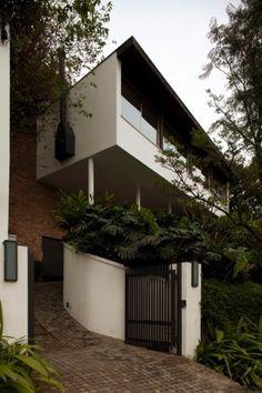 Uma caixa de concreto com janelas rasgadas em toda a extensão da fachada define o volume sobre pilotis que dá corpo à casa paulistana projetada por João batista Vilanova Artigas em 1944. Na construção, a empena cega em uma das laterais apóia a chaminé da lareira