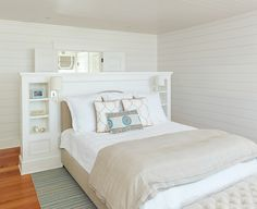 Interesting use of a built-in headboard as room divider just inside the doors.   Coastal bedroom | House of Turquoise: Structures Building Company