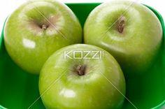 granny smith apples on a green platter - Three Granny Smith apples sitting in a green plastic container.
