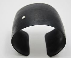 1 Sapphire Black Chrome Cuff by Dennis Higgins. This cuff is black chrome over silicon bronze. It has one 2.5mm white sapphire slightly offset on the surface. The cuff has a wonderful sheen which can be maintained with hand cream. It is a simple and chic piece of black jewelry.
