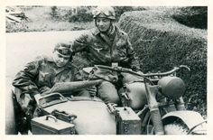 Two soldiers pausing to check their map with their BMW R75