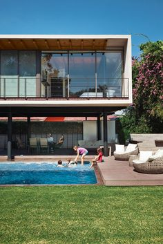 On an idyllic afternoon, members of the Oropeza and Castillo clans splash in the backyard pool framed by Trex decking and outfitted with furniture by Móbica.  Photo by: Mauricio Alejo