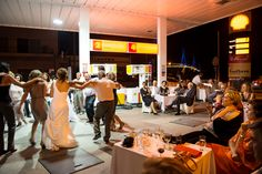 This is an image of a wedding in Greece, and where the groom decided in order to save money, to hold the wedding at the gas station he owns.  So to me this is a 'beautiful' image simply due to the quirkiness and originality!  Imagine, an outdoor wedding amongst gas pumps??  How uniquely fun!  Photo by Nick Hannes.