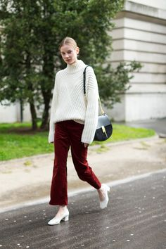 Cropped red pants with a turtleneck sweater, white pumps, and a Chloe bag.
