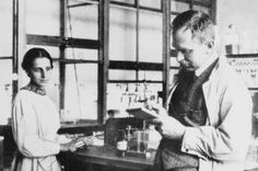 Lise Meitner and Otto Hahn in their lab. Black and white photo.