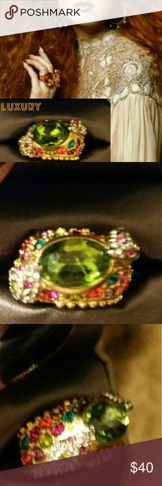 GLAM RING Incrideble color packed into one gorgeous piece. This ring is truly a stunner. The central stone is a vibrant green with tons of depth, and it is framed by Diamante snakes with pink eyes on either side.  Set in gold and surrounded by vibrant pink, teal, red, and green stones, this ring is definitely made for the connoisseur of the unique and the bold. It is open on the bottom, but is heavy and very well made. It's a size 7, and I believe you can adjust it some, but not like much…